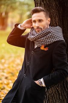 De knappe man leunt tegen de boom en strekt zijn haar in een donkerblauwe jas