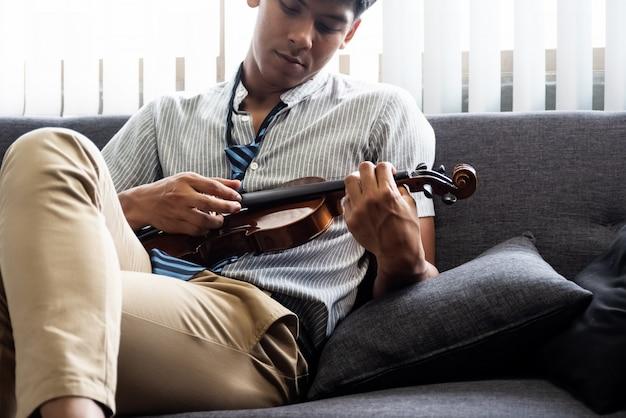 De knappe man met viool in de hand en te drukken, voor het controleren van het akoestische instrument, voor te bereiden voor het spelen van muziek