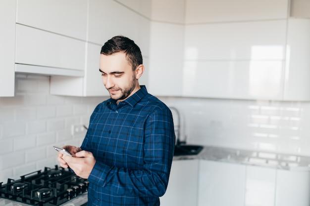 De knappe man op keuken glimlacht in de ochtend en bekijkt slimme telefoon