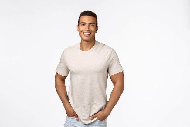 De knappe mannelijke atleet in toevallige t-shirt, houdt handen en zakken in die met gelukkig glimlachen