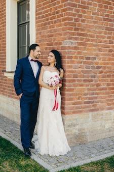 De knappe mannelijke bruidegom bekijkt met grote liefde zijn bruid