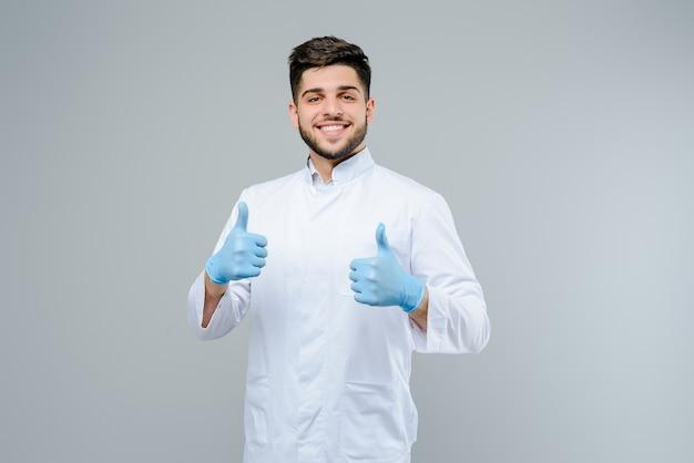 De knappe mannelijke medische arts in handschoenen toont duimen die omhoog over grijze achtergrond worden geïsoleerd