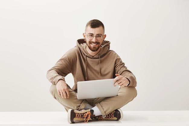 De knappe mannelijke student zit gekruiste benen en met behulp van laptop