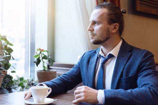 De knappe mens drinkt koffie binnen koffiestaaf kijkend in het venster. jonge mode-man tijdens de lunchtijd