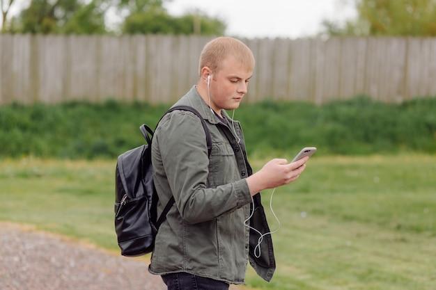 De knappe mens gebruikt telefoon openlucht houten muur