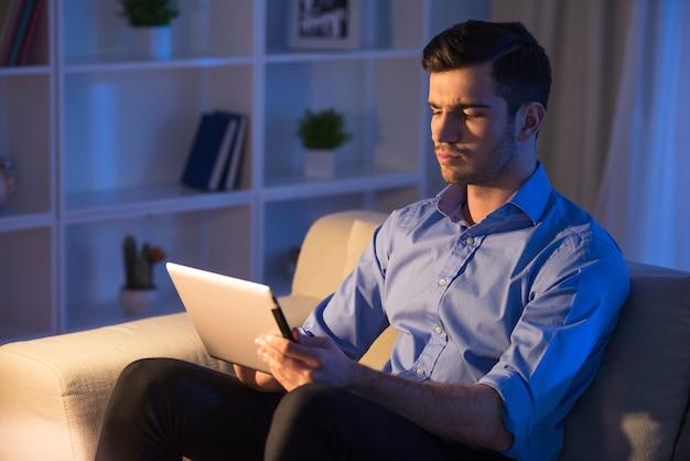 De knappe mens gebruikt thuis digitale tablet.