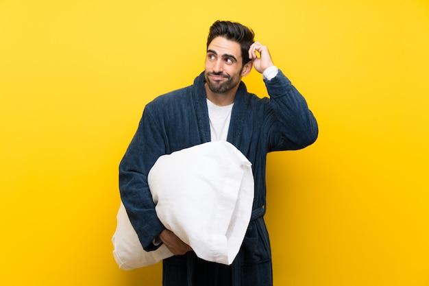 De knappe mens in pyjama's die twijfels hebben en verwart gezichtsuitdrukking