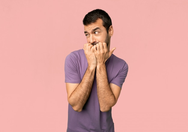 De knappe mens is een klein nerveus en doen schrikken zettend handen aan mond op geïsoleerde roze achtergrond