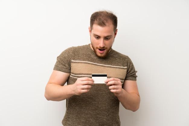 De knappe mens isoleerde witte muur die een creditcard houdt