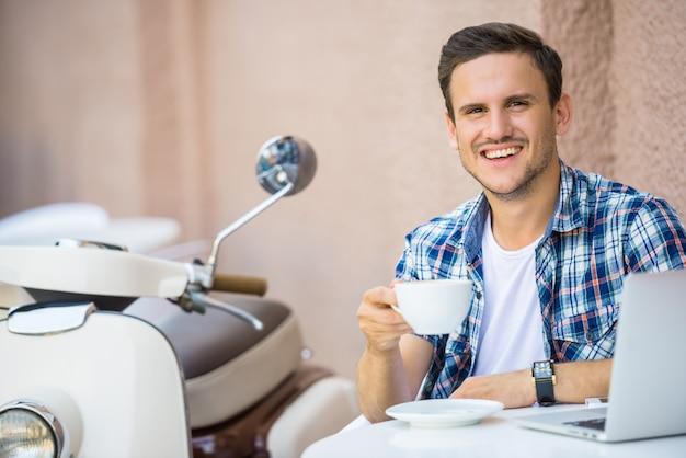 De knappe mens ontspant in koffie en drinkt koffie.