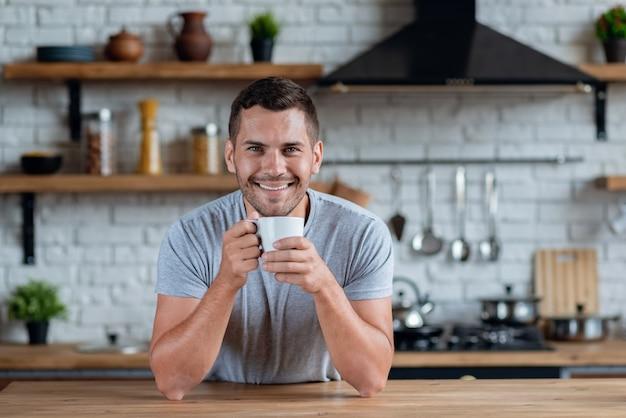 De knappe mens zit bij de keukenlijst met kop van ochtendthee of koffie en het glimlachen