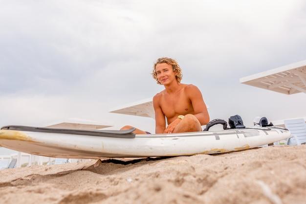 De knappe mens zit op het strand met witte lege surfende raad wacht op golf om vlek op zee oceaankust te surfen. concept van sport, fitness, vrijheid, geluk, nieuw modern leven, hipster.