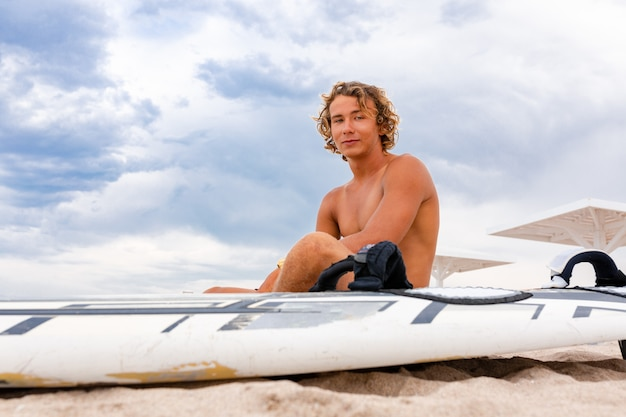 De knappe mens zit op het strand met witte lege surfende raad wacht op golf om vlek op zee oceaankust te surfen.