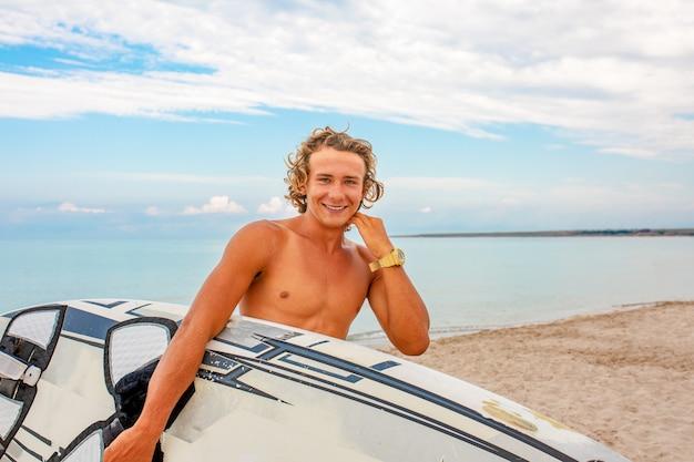 De knappe mensengang met witte lege surfende raad wacht op golf om vlek op zee oceaankust te surfen. concept van sport, fitness, vrijheid, geluk, nieuw modern leven, hipster.
