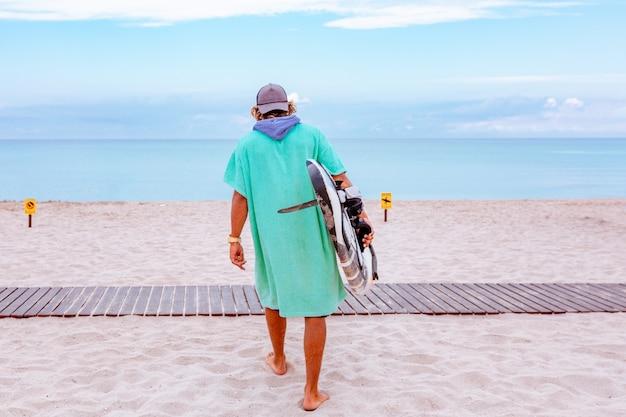 De knappe mensengang met witte lege surfende raad wacht op golf om vlek op zee oceaankust te surfen.