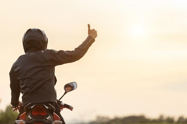 De knappe motorrijder draagt leerjasje, houdend helm op de weg