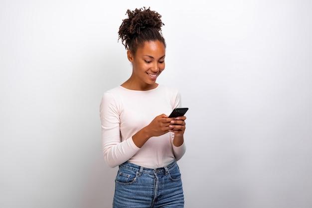 De knappe mulatvrouw bevindt zich houdend mobiele telefoon bekijkend het scherm