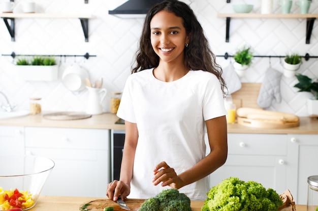 De knappe mulatvrouw glimlacht en houdt een mes op de moderne keuken gekleed in wit t-shirt, dichtbij de lijst met verse groenten