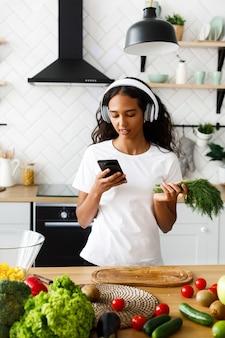 De knappe mulatvrouw kijkt op smartphone en groen, in grote draadloze hoofdtelefoons, dichtbij de lijst met verse groenten