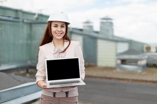 De knappe onderneemster in beige kostuum bevindt zich op het dak en toont lege laptop