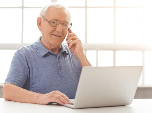 De knappe oude zakenman spreekt op de mobiele telefoon.
