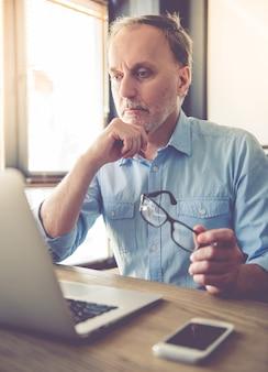 De knappe rijpe vermoeide zakenman gebruikt laptop