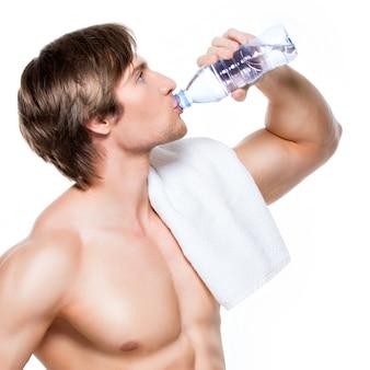 De knappe spier shirtless sportman drinkt water - dat op witte muur wordt geïsoleerd.