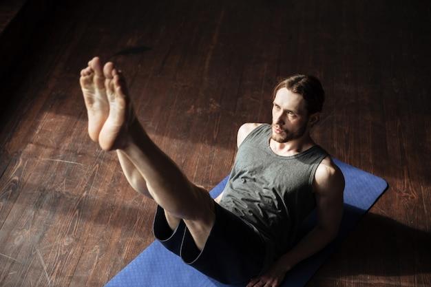 De knappe sterke sportman in gymnastiek maakt yogasportoefeningen