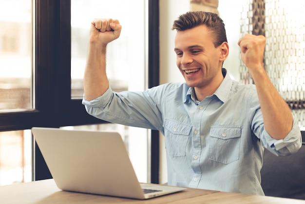 De knappe succesvolle jonge zakenman heft zijn handen op