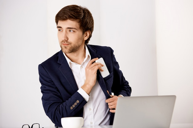 De knappe succesvolle zakenman zit bureau, drinkt koffie en controleert post in laptop, zette mobiele telefoon in jaszak