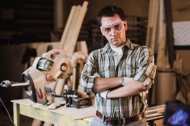 De knappe timmerman in beschermende glazen bekijkt camera en glimlacht terwijl status dichtbij zijn houten voorwerp in de workshop