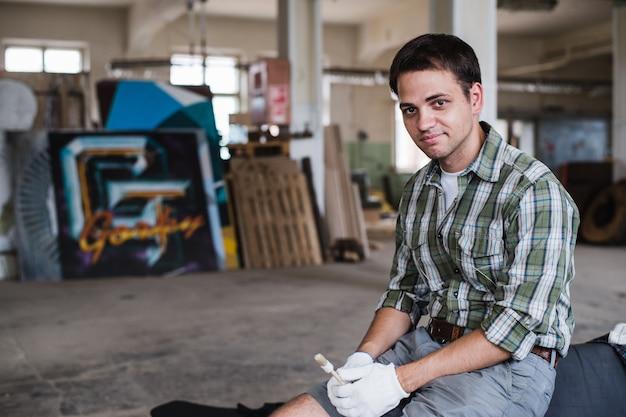 De knappe timmerman in beschermende glazen kijkt en glimlacht terwijl status dichtbij zijn houten voorwerp in de workshop