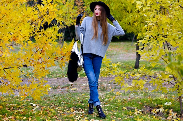 De knappe vrouw met lang haar draagt jeans en handschoenen die zich in zelfverzekerde houding op aardachtergrond bevinden. buiten foto van vrij vrouwelijk model in trendy grijze trui wandelen in het park in herfstdag.