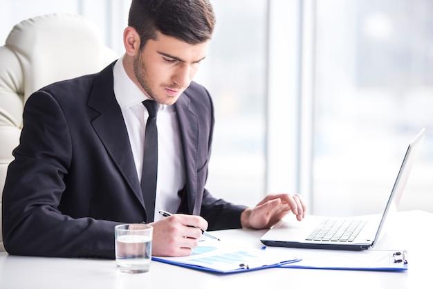 De knappe zakenman werkt met laptop in bureau.
