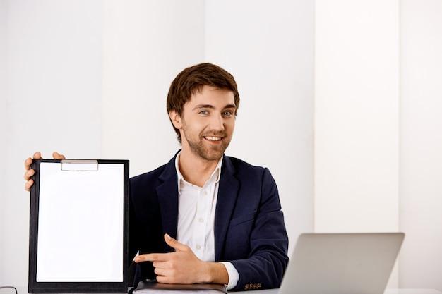 De knappe zekere, glimlachende jonge mens die zijn grafiek voorstelt, zit bureau, wijzend vinger op klembord