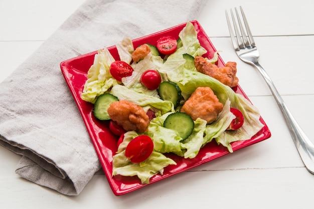 De knapperige salade van de kippenpopcorn die met groenten in rode plaat met servet en vork wordt verfraaid