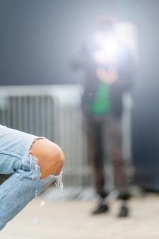 De knie van de vrouw in spijkerbroek. een model in spijkerbroek poseert voor een fotograaf. moderne trendy jeugdstijl.
