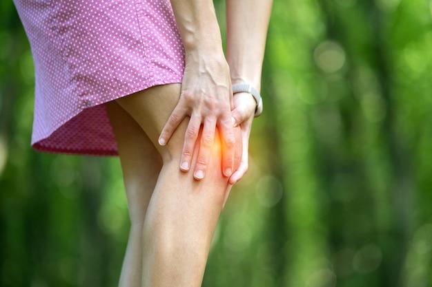 De knie van de vrouwenholding met handen die sterke pijn hebben.