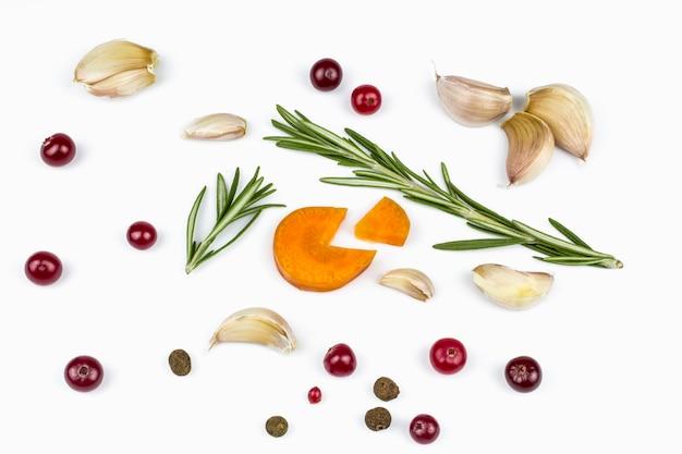 De knoflook, gesneden wortel, verse takken van rozemarijn en bes van cranberry, mengsel van paprika's geïsoleerd op een witte achtergrond.