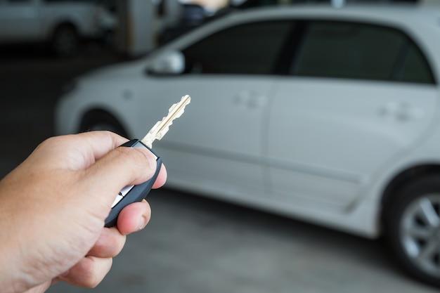 De knoop van de handholding op de verre auto bij parkeerterreinachtergrond