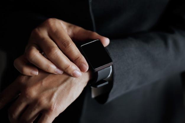 De knoop van de zakenmanpers vindt baan op slim horloge in hand, donkere achtergrond
