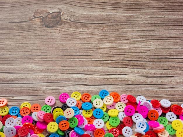De knoppen meerkleurig op houten tafel voor doe-het-zelf of handgemaakt concept.