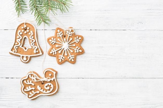 De koekjes die van de kerstmispeperkoek op sparren over witte houten achtergrond hangen, kopiëren ruimte.