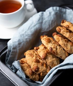 De koekjes met noten op de grijze achtergrond van de bakselschotel sluiten omhoog
