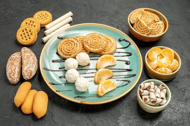 De koekjes van de vooraanzichtsuiker met suikergoed en koekjes op het grijze koekje van het lijstsuikergoed