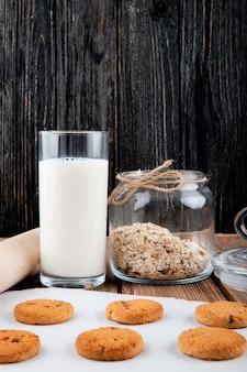De koekjes van het zijaanzichthavermeel op calqueerpapier met melkhavermeel en een deegrol op een houten achtergrond