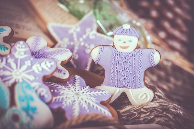 De koekjes van peperkoekkerstmis, sneeuwvlokken gingerman. gebreide sjaal en kaneelstokjes.