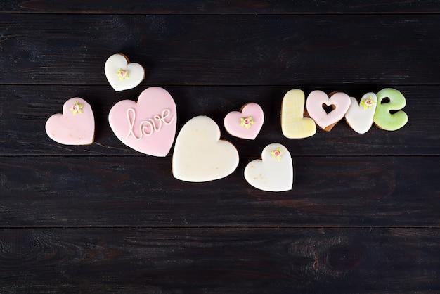 De koekjes van valentine in vorm van hart op donkere houten achtergrond