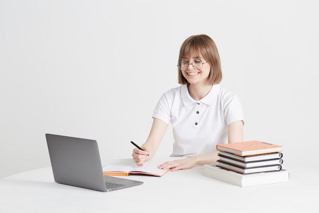 De koele gelukkige vrouw gaat thuis online opleidingszitting door. onderwijs op afstand op een laptop. blijf thuis lessen.