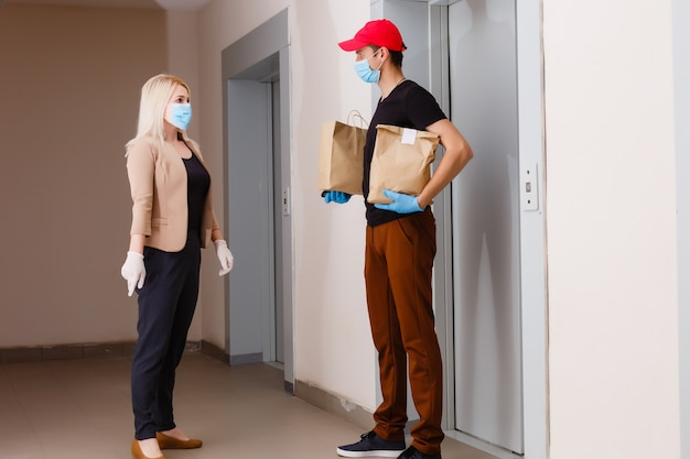 De koerier bezorgt het pakket aan de deur, in latex handschoenen, contactloze bezorging tijdens de quarantaineperiode